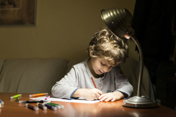 Cute boy drawing on paper while at home