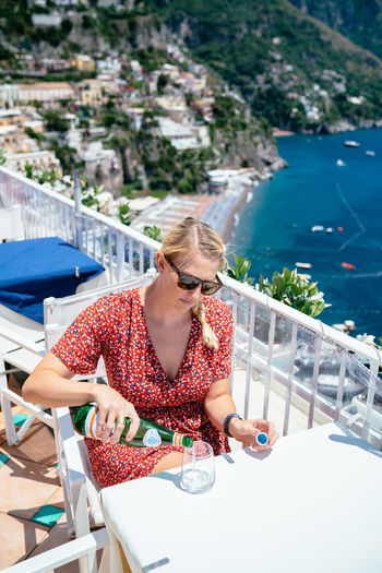 Woman pouring beer in glass while sitting at restaurant against sea