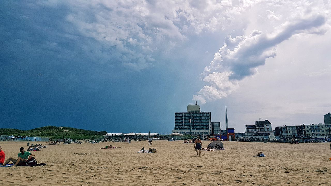 beach, sand, sky, cloud - sky, real people, architecture, day, outdoors, men, large group of people, vacations, built structure, building exterior, nature, leisure activity, travel destinations, sea, lifestyles, city, beach volleyball, beauty in nature, people