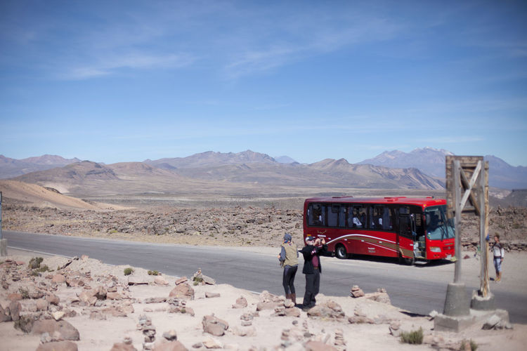 Tourists Photographing On Dry Landscape In Front Of Bus