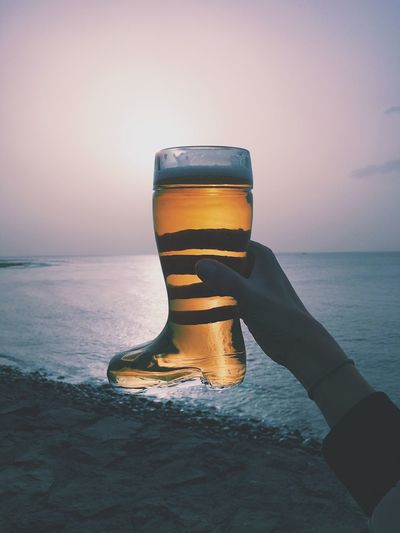Cropped hand of woman holding boot shape beer glass at beach against sky during sunset