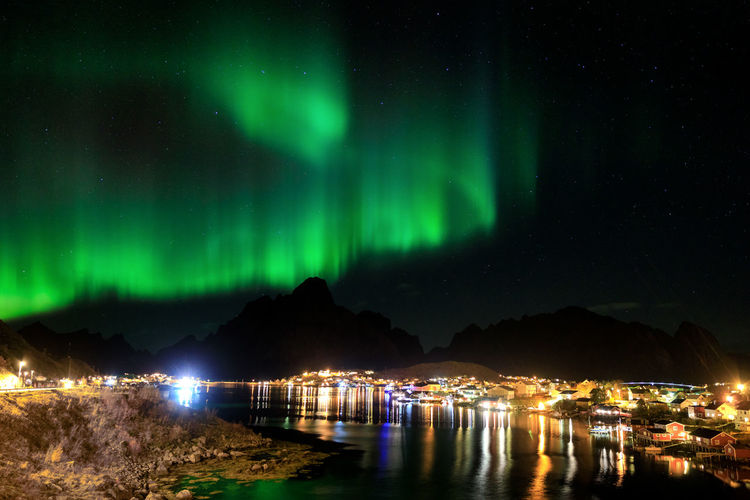 Northern lights over the vilage of Reine, Lofoten, Norway Lofoten Norway Polar Light Northern Lights Aurora Polaris Aurora Borealis Night Illuminated Sky Water Green Color Scenics - Nature Beauty In Nature No People Star - Space Reflection Space Astronomy Tranquility Nature Architecture Tranquil Scene Mountain Lake Majestic