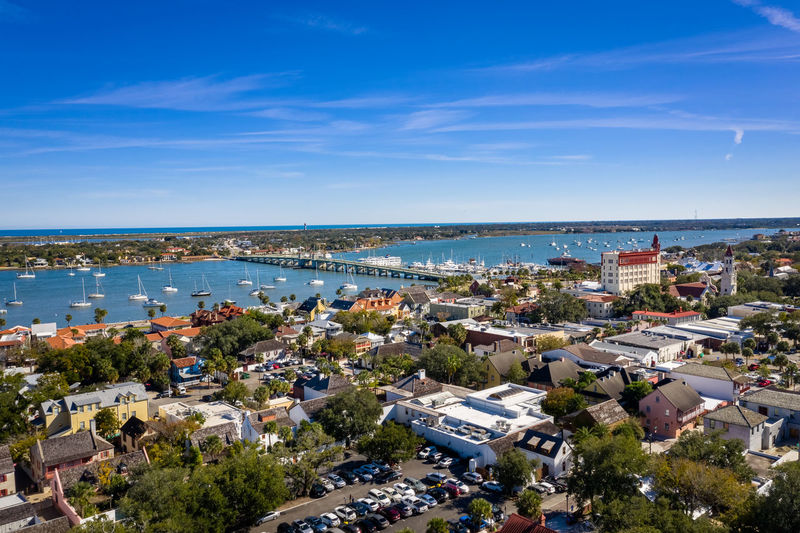 High angle view of townscape by sea against blue sky