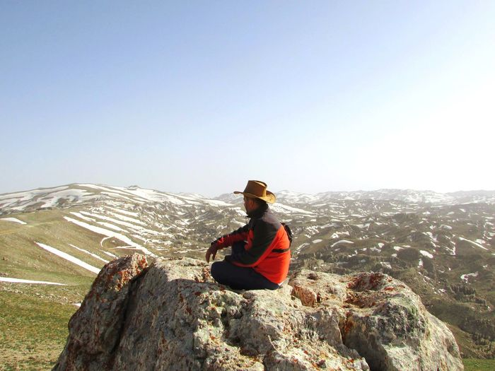 Man sitting on rock against mountain range against clear sky