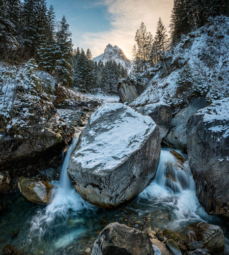 View of stream flowing through rocks during winter