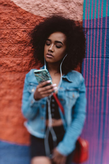 Afro Black Woman Listening To Music Music Adult Beautiful Woman Casual Clothing Front View Hair Hairstyle Holding Indoors  Leisure Activity Lifestyles Looking One Person Phone Real People Standing Technology Waist Up Wall - Building Feature Women Young Adult Young Women