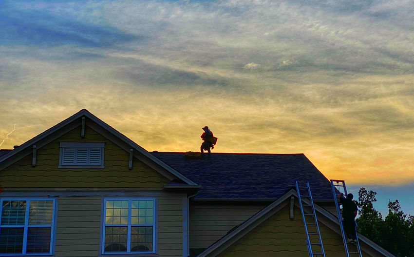 Low angle view of man standing outside house against sky