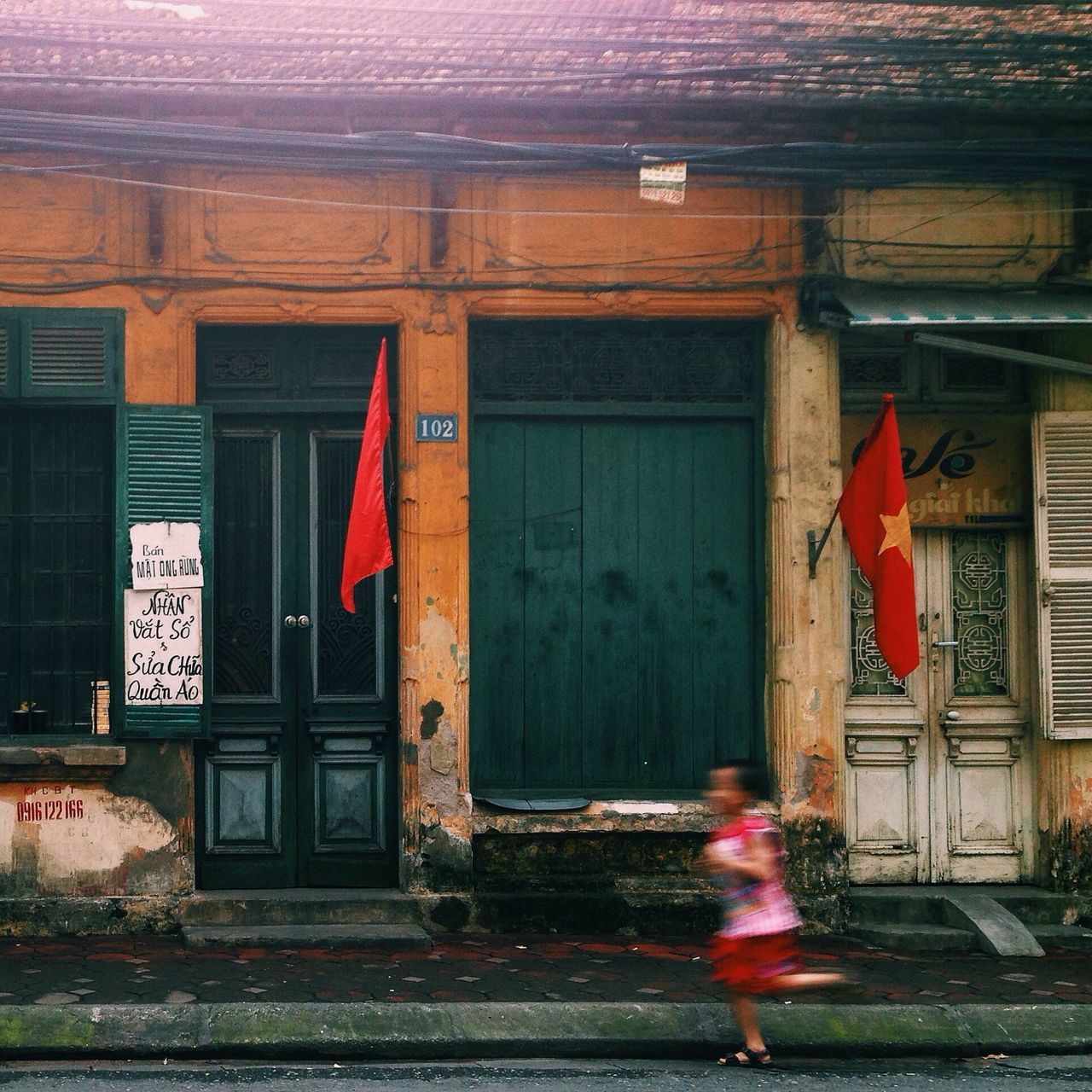 Side view of a blurred girl running against house
