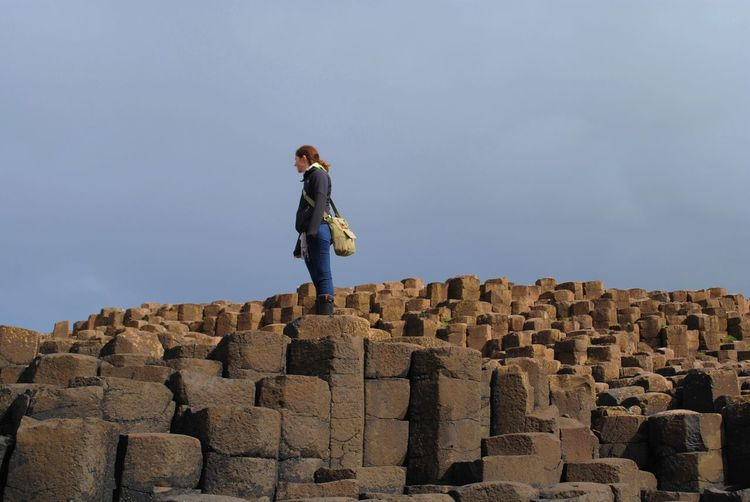 Low angle view of man standing on giants causeway against sky