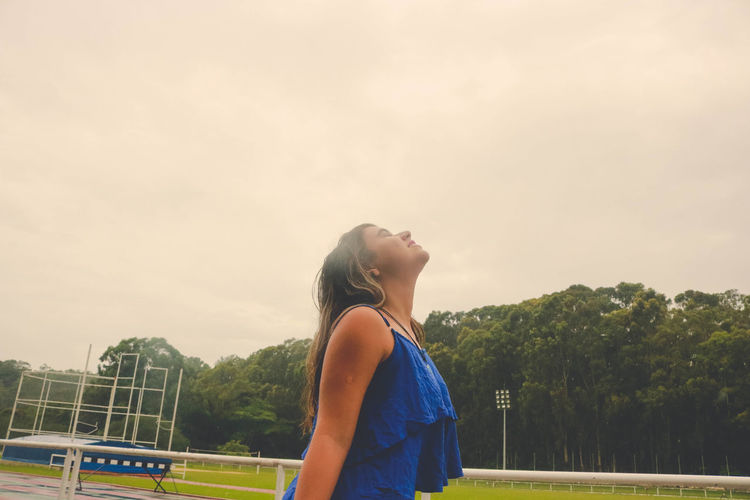 Side view of young woman standing at stadium against sky