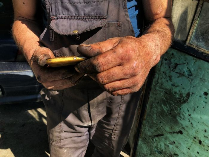 Midsection of mechanic using mobile phone
