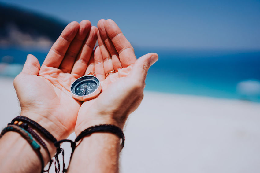 Open hand palms with metal compass on the sandy beach. Searching your way concept. Blue sea in background. Point of view pov Human Hand Human Body Part Water Hand Sea Body Part Sky One Person Watch Nature Horizon Over Water Human Finger Finger Close-up Holding Day Outdoors Destiny Way Direction Concept Choise Tanned Compass Travel