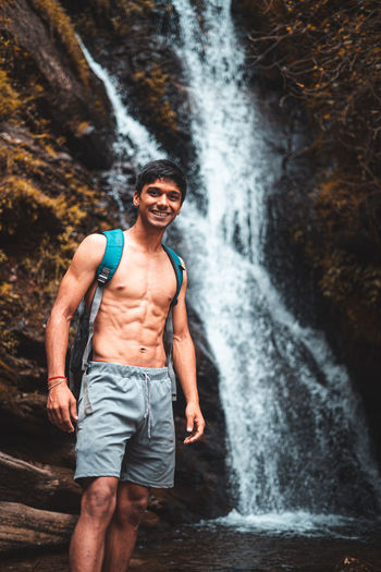 Full length of man standing against waterfall