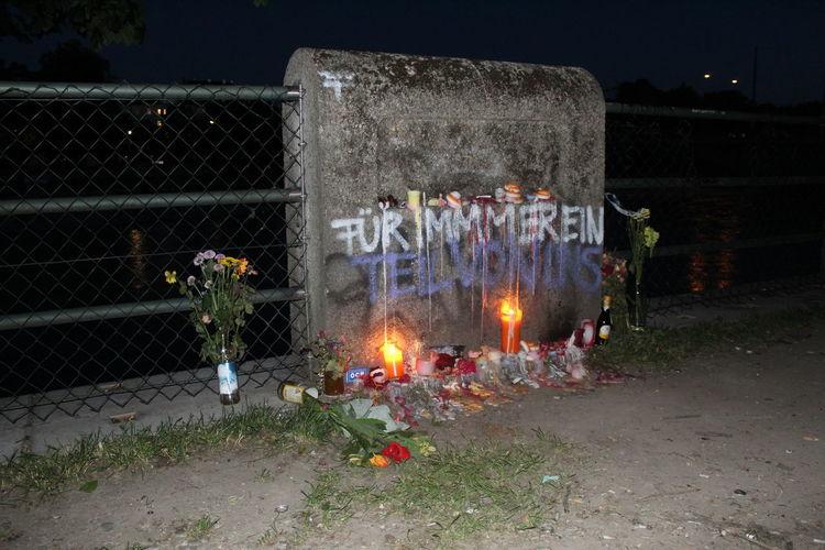 Illuminated candles on wall at night