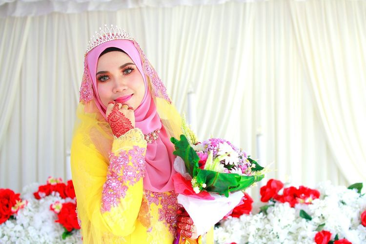 Portrait of beautiful bride wearing hijab with bouquet against curtain