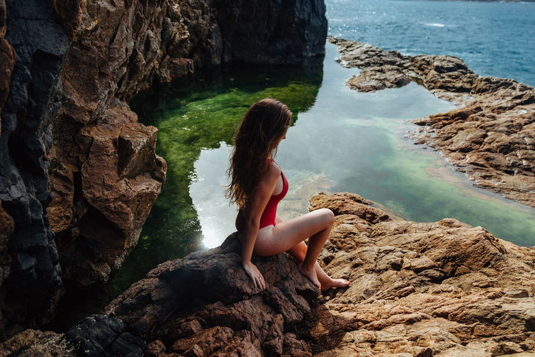 High angle view of woman sitting on rock over sea
