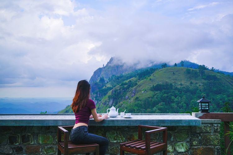 Woman Sitting At Table Against Sea And Mountains