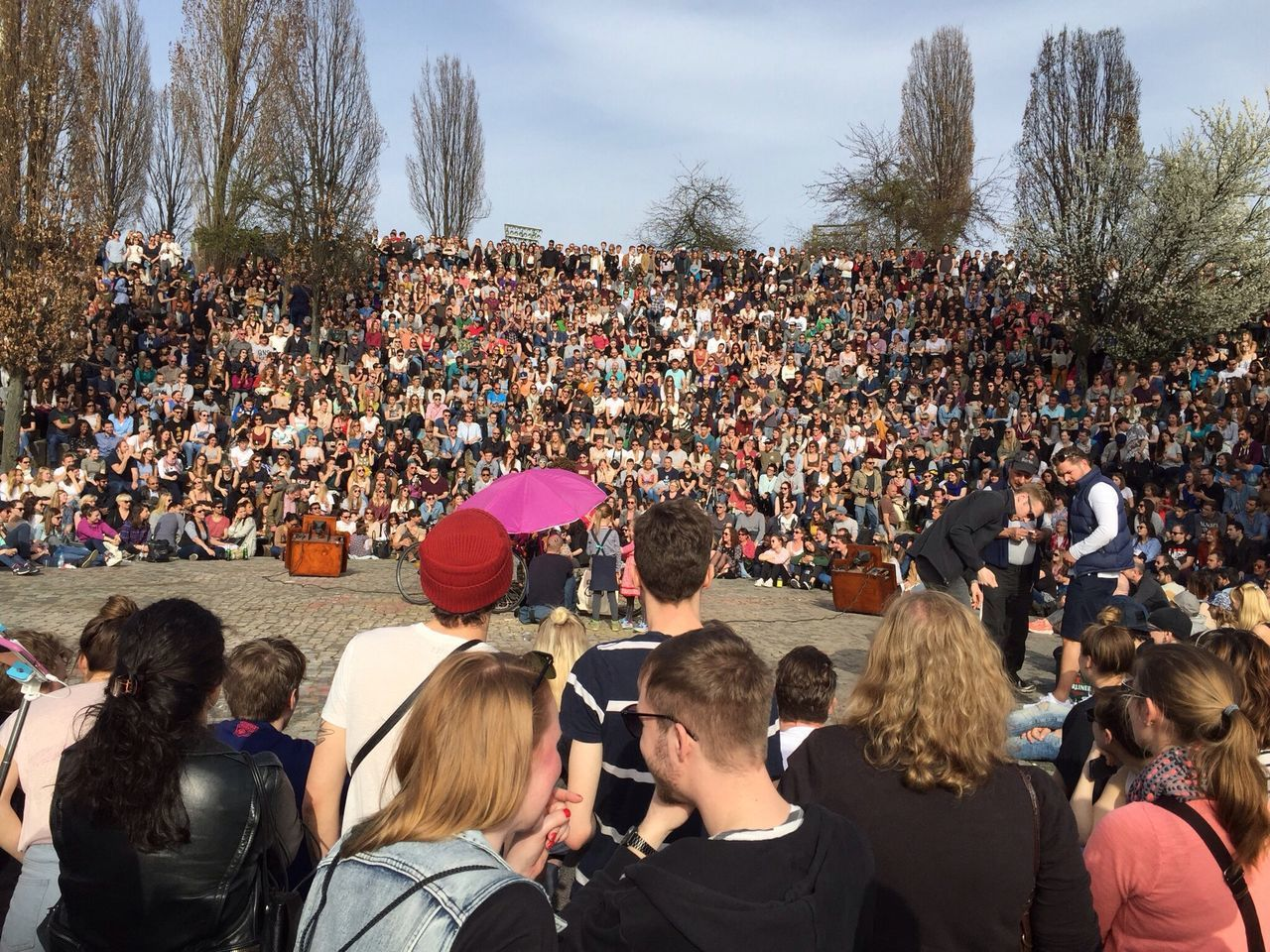 large group of people, crowd, watching, leisure activity, women, music, men, arts culture and entertainment, spectator, togetherness, audience, day, fan - enthusiast, real people, outdoors, tree, people, sky, adult, adults only