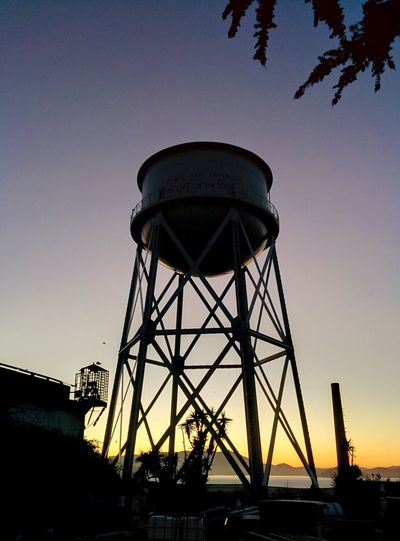 Low angle view of water tower against clear sky at sunset