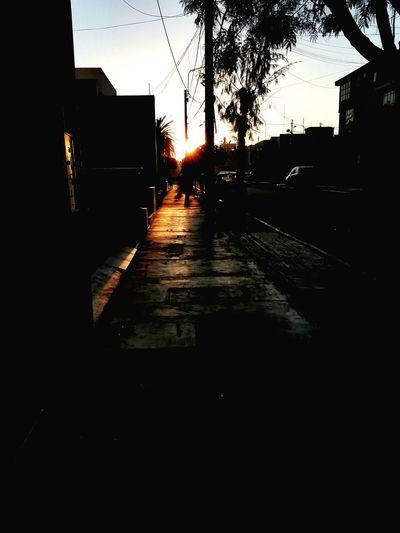 Street amidst silhouette buildings against sky during sunset
