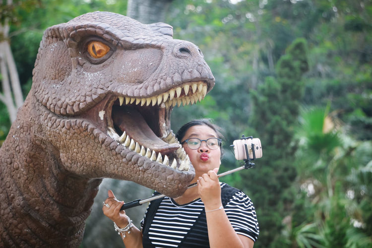 Woman puckering while taking selfie with dinosaur statue in park