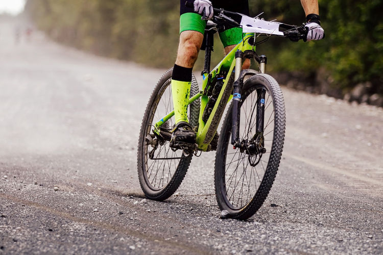 Cyclist rider on mountain bike downhill on gravel road cross-country competition