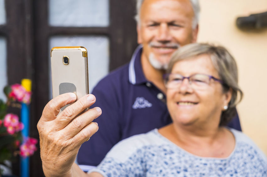 cheerful happy old senior adult man and woman taking selfie with the phone at home. smiles and happiness using phone to communicate with parents and son or daughters. video conference and live call. Adult Beard Communication Couple - Relationship Focus On Foreground Front View Glasses Headshot Healthcare And Medicine Holding Males  Mature Men Men Portrait Selfie Senior Adult Senior Couple Senior Women Smiling Technology Togetherness Two People Using Phone Wireless Technology Women