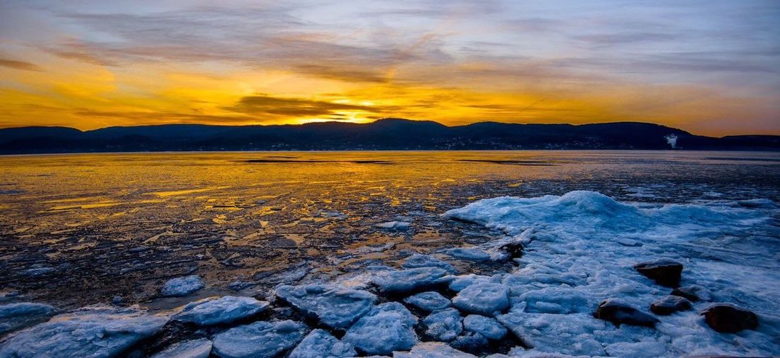 Scenic view of frozen lake against dramatic sky during sunset