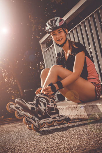Portrait of smiling young woman wearing roller skates