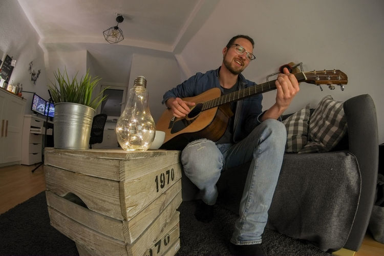Young male having fun while playing acoustic guitar in cosy living room Guitar Player Playing Guitar Acoustic Guitar Guitar Guitarist Musical Instrument Music Sitting Playing Holding Musician Living Room Musical Equipment Young Adult Having Fun Analogue Sound
