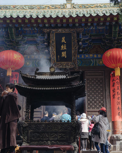 People in temple outside building