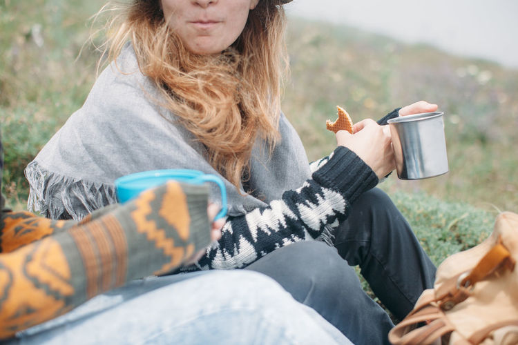 Friends having their hot cup of tea outdoors Break Breakfast Close-up Cup Day Eating Female Friends Holding Meal Nature Outdoors Resting Tea Tea Time Warm Clothing Wind People Together Traveling Home For The Holidays