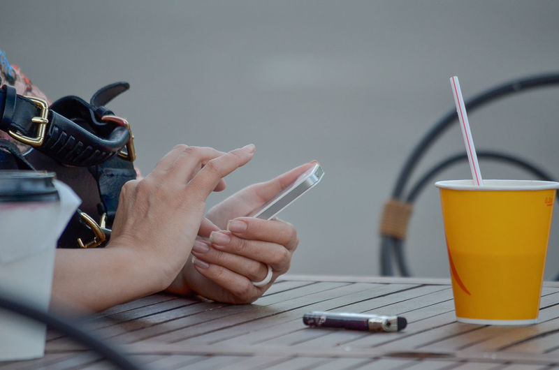 Cropped Hands Of Woman Using Phone At Table