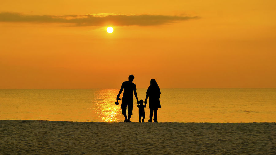 Silhouette family walking at beach against sky during sunset