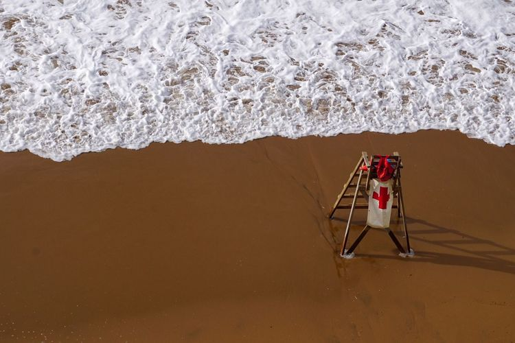 High Angle View Of Lifeguard Chair On Shore At Beach