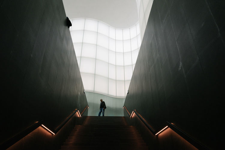 Silhouette people walking on staircase in building