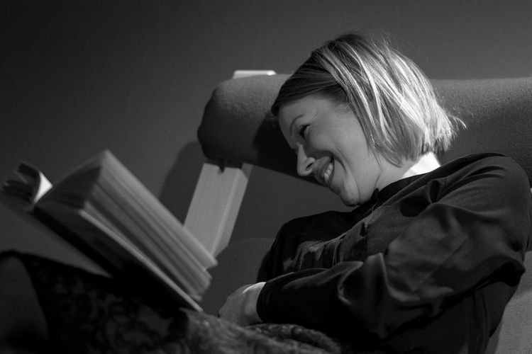 Close-up of smiling woman with book sitting on chair at home