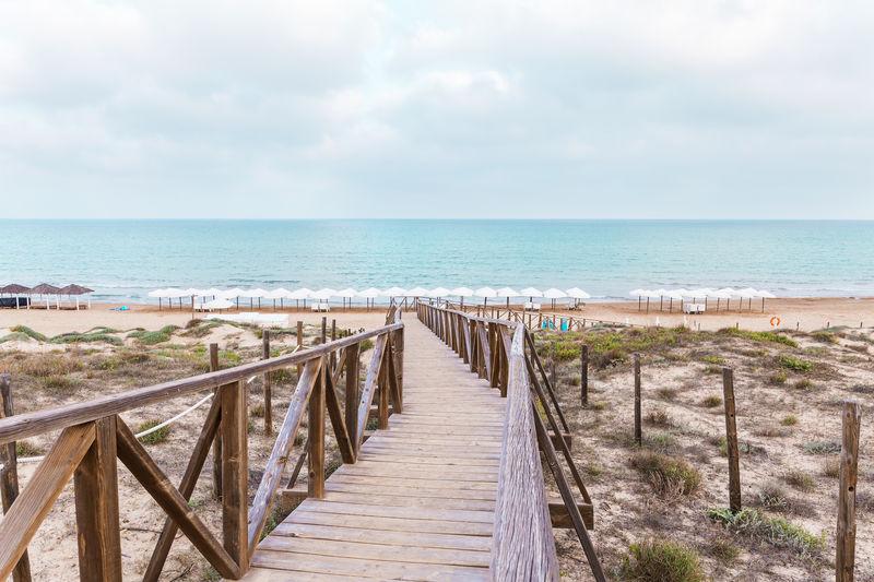 Boardwalk on beach against sky