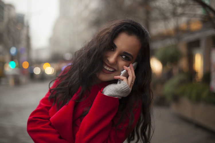 Happy young woman talking on mobile phone while standing on city street