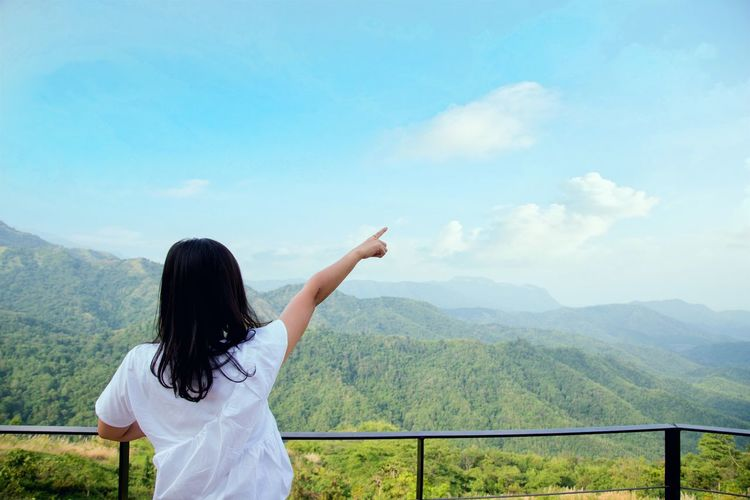 Rear view of woman with arms raised against mountains