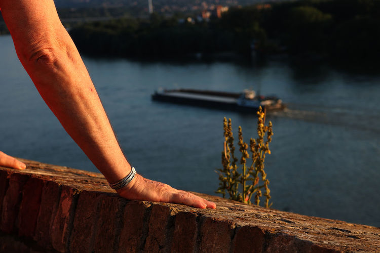 Cropped hands on retaining wall by river