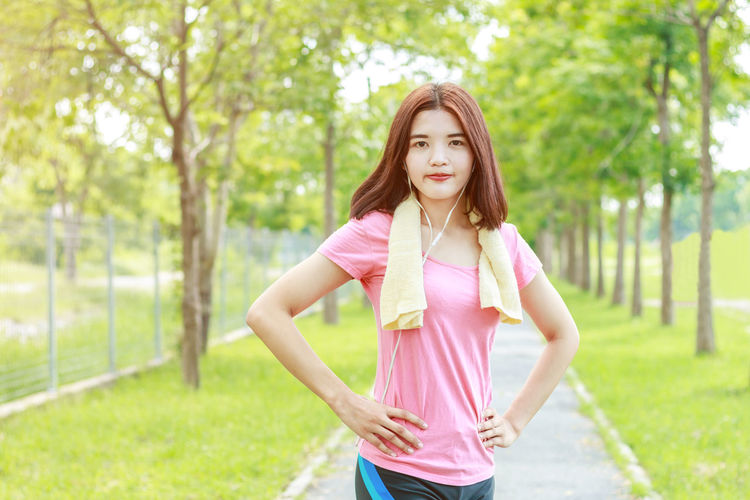 Portrait Of Woman Listening Music While Standing On Footpath Against Trees