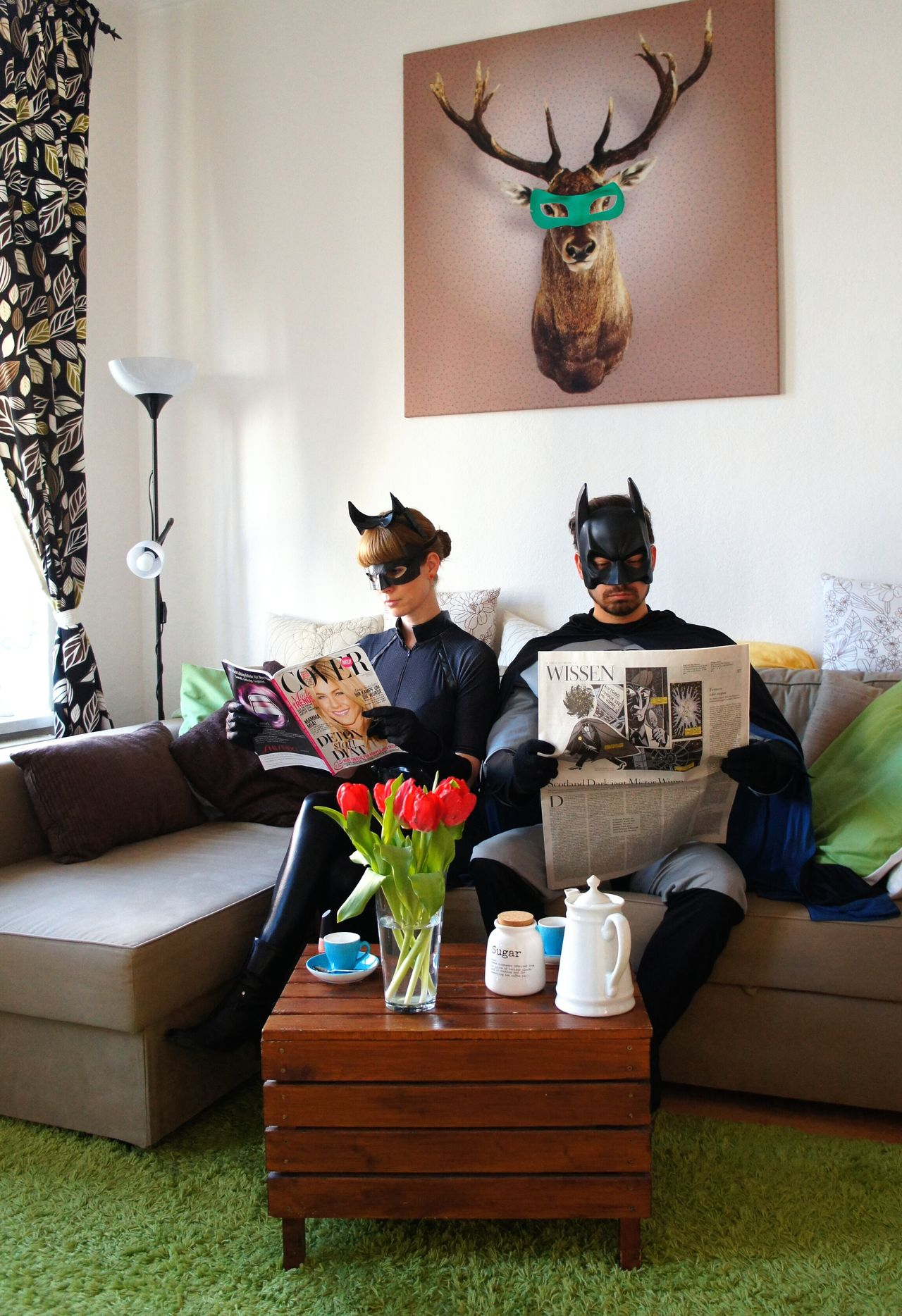 Couple in batman costumes reading newspapers at home