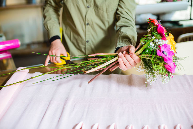 Midsection of florist holding making bouquet at table in flower shop