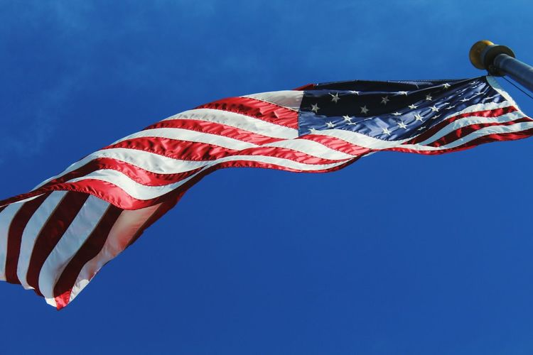 Directly below shot of american flag waving against sky