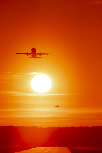 Airplane taking off at sunset Air Vehicle Sunset Airplane Flying Sky Orange Color Sun Transportation Mode Of Transportation Beauty In Nature Silhouette Travel Mid-air Sunlight Nature Scenics - Nature Taking Off Outdoors Yellow Red Aerospace Industry