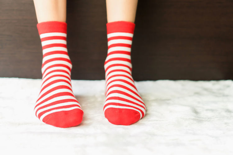 Low section of woman wearing red and white striped socks at home