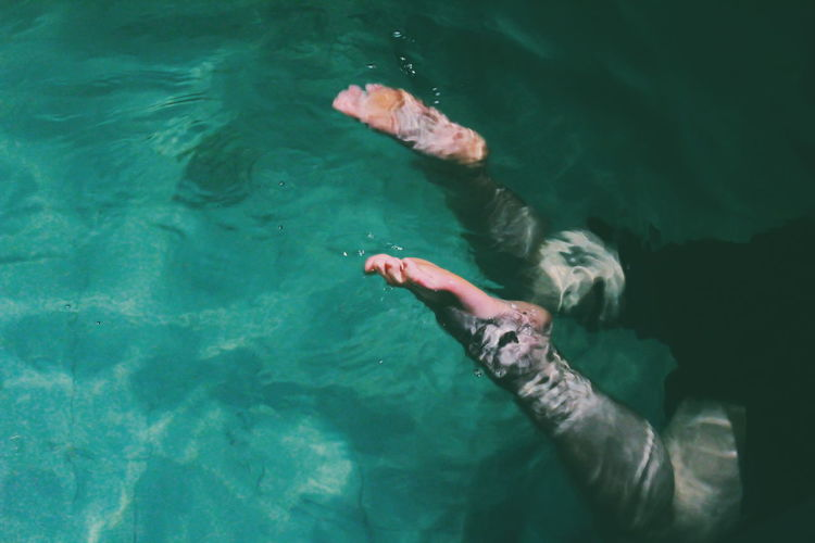 Low section of person swimming in sea