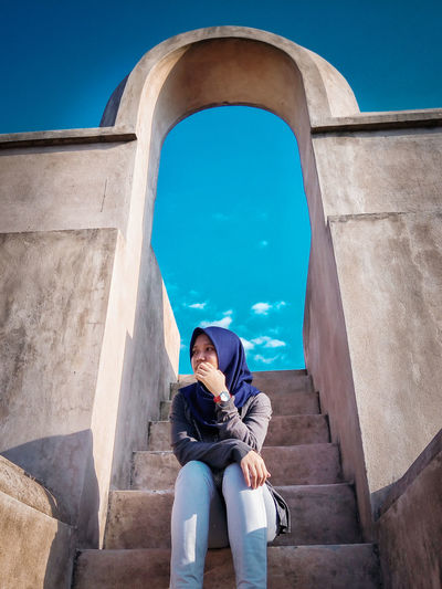 Low angle view of woman wearing hijab sitting on steps against blue sky