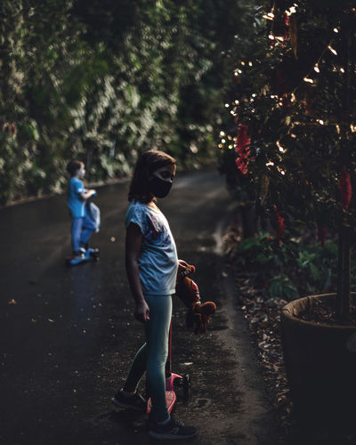 Side view of siblings with push scooters standing on road during christmas